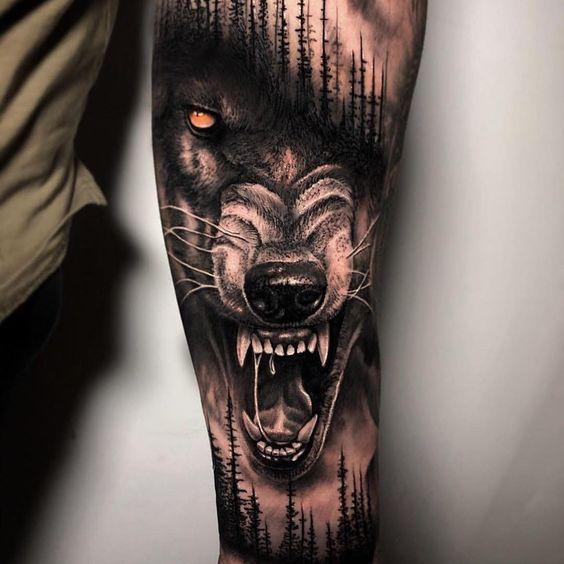 Tatuaż realistyczny wilka w lasie na przedramieniu