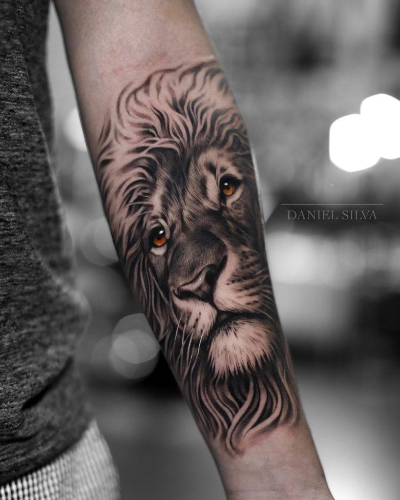 Graficzny Tatuaż głowa lwa naprzedramieniu zpomarańczowymi oczami