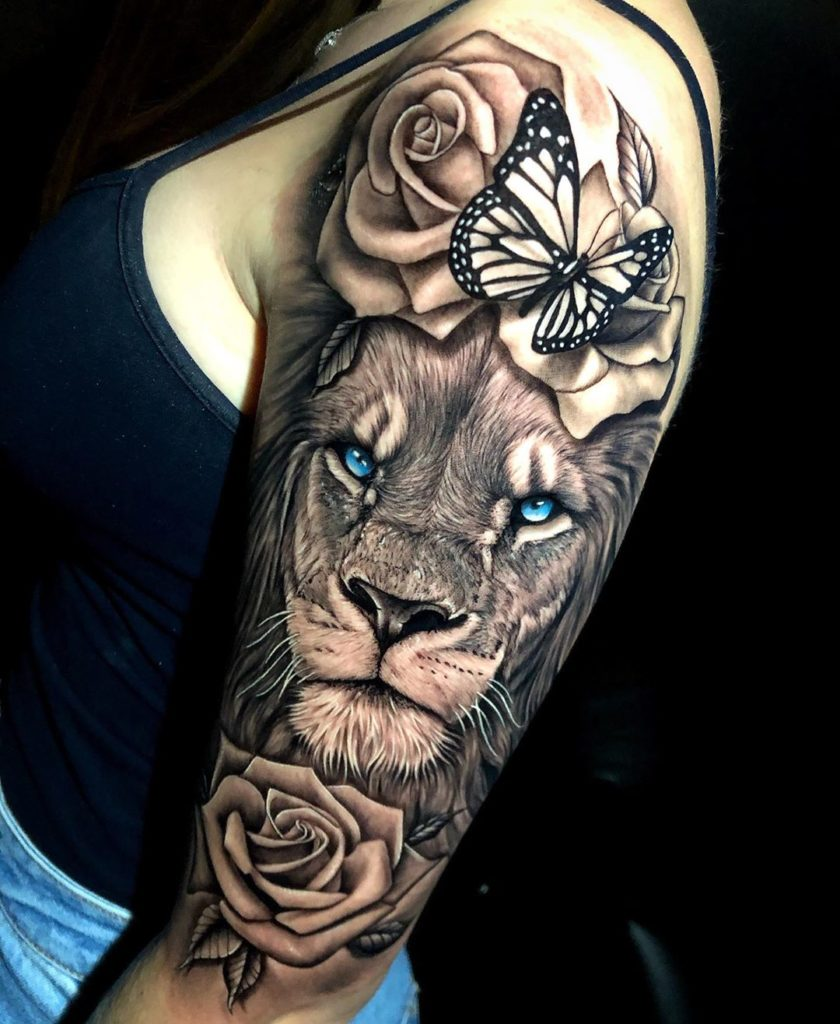 Tatuaż Lew niebieskimi oczami zkwiatami różą, motylkiem naprzedramieniu znaczenie dla mężczyzn ikobiet