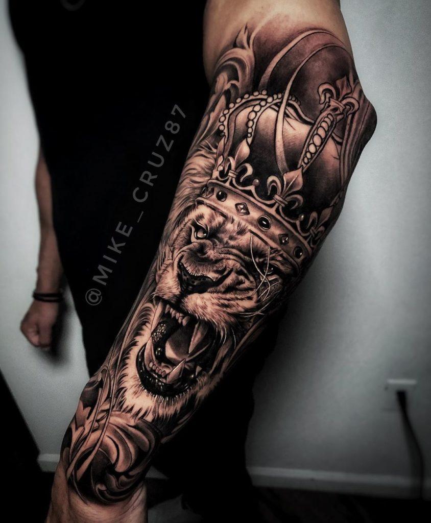 Tatuaż Lew zkoroną nazewnętrznej stronie przedramieniu