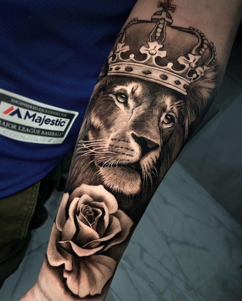 Tatuaż Lew zkwiatami różą ikoroną naprzedramieniu znaczenie dla mężczyzn ikobiet