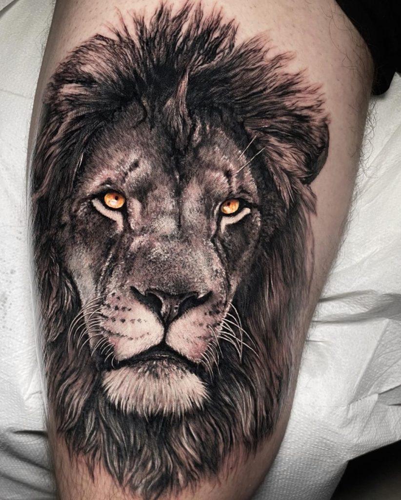 Tatuaż głowa lwa nanodzę lydce zżółtymi oczami