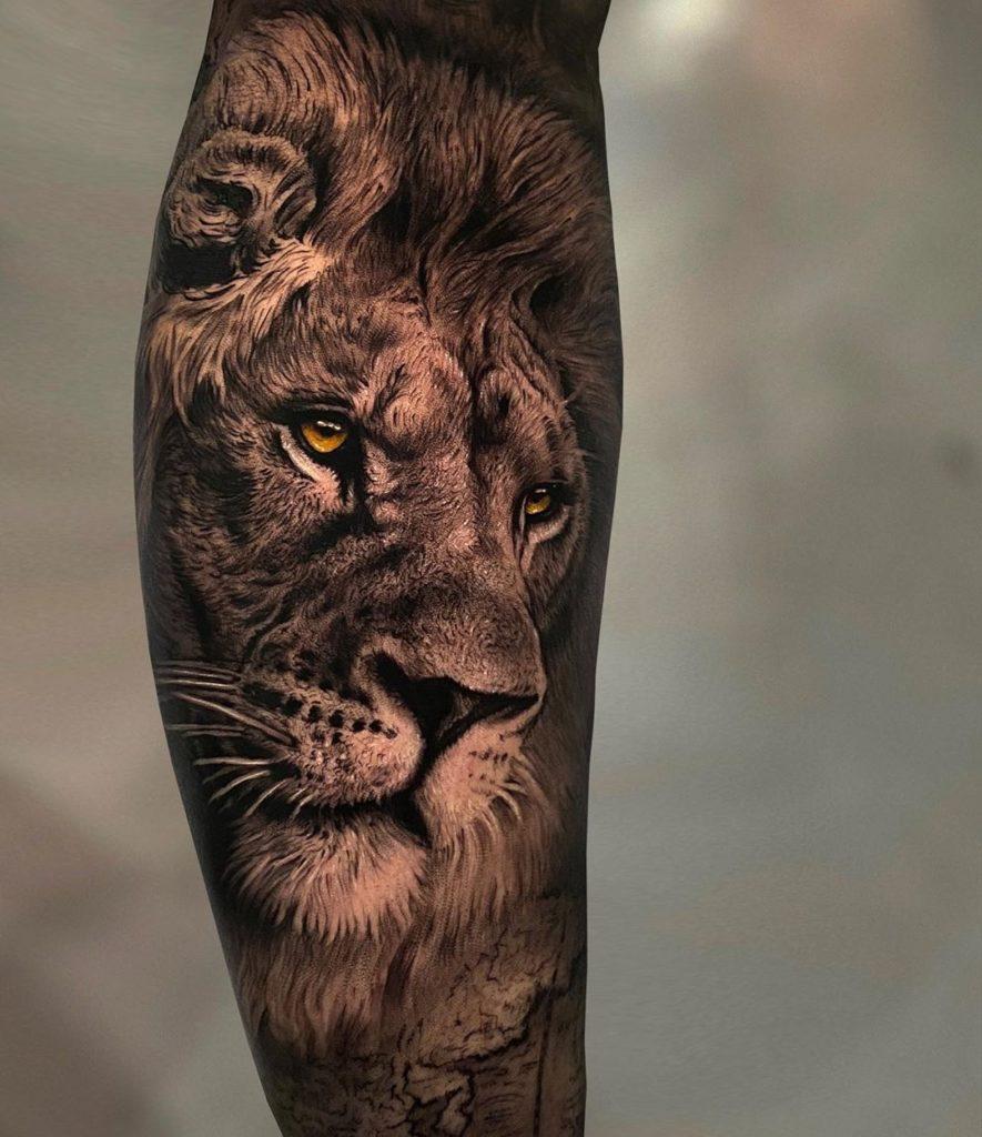 Tatuaż głowa lwa nanodzę lydce zpomarańczowymi oczami