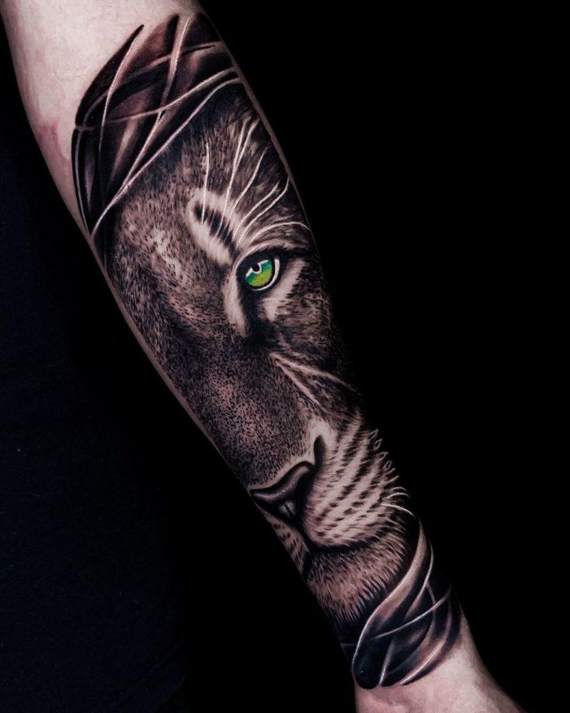 Tatuaż głowa lwa naprzedramieniu zkolorowymi oczami