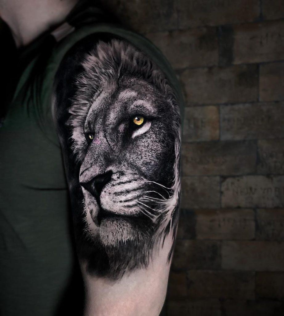 Tatuaż głowa lwa naramieniu zpomarańczowymi oczami
