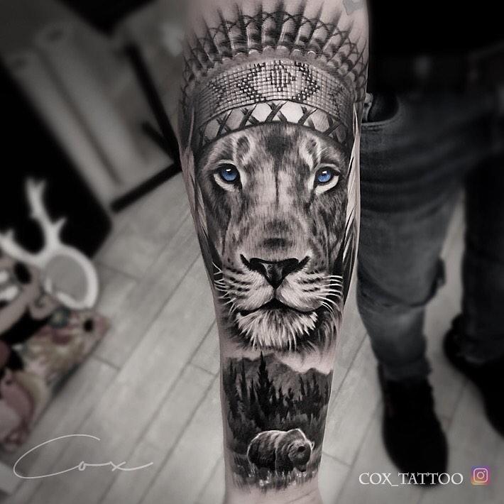 Tatuaż głowa lwa zpiórami zniebieskimi oczami iniedźwiedziem ilasem Znaczenie dla mężczyzn ikobiet