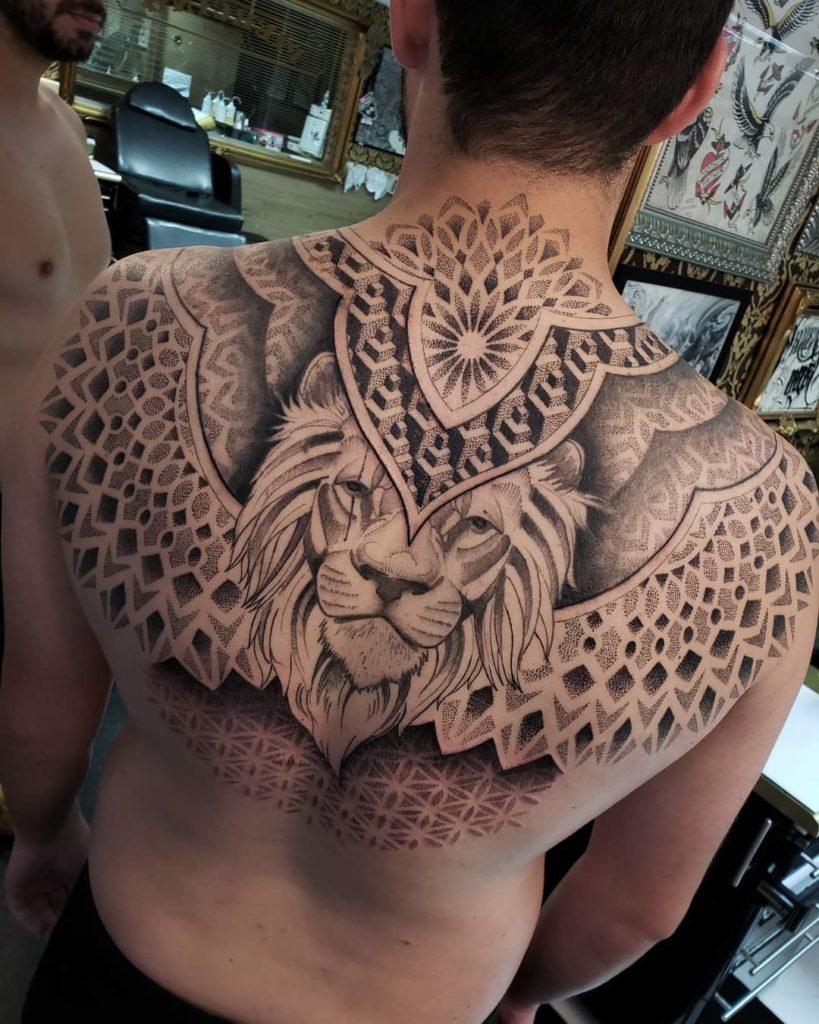 Tatuaż lwa wgraficznej stylistyce zdotworkiem naplecach Znaczenie dla mężczyzn ikobiet