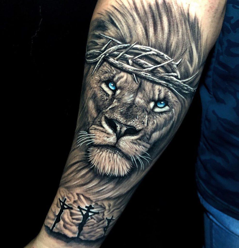 Tatuaż lwa zniebieskimi oczami, zkrzyżem Jezus znaczenie dla mężczyzn ikobiet