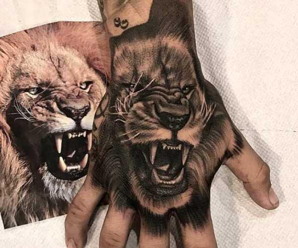 Tatuaż lwa zotwartą paszczą nadłoni