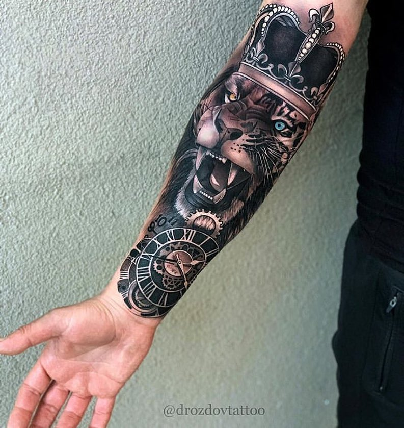 Tatuaż warczący lew zkolorowymi oczami, niebieski, żółty naprzedramieniu znaczenie dla mężczyzn ikobiet
