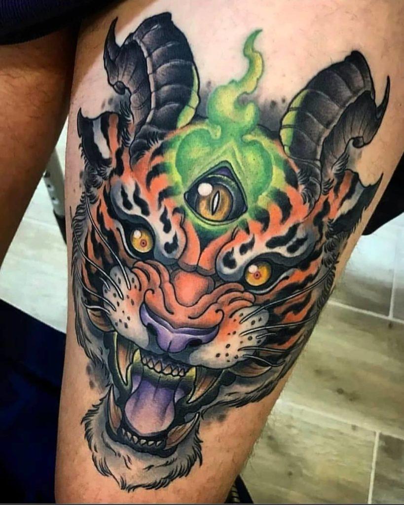 Tatuaż kolorowy tygrys zrogami naudzie, biodrze zżółtymi oczami męski, kobiecy