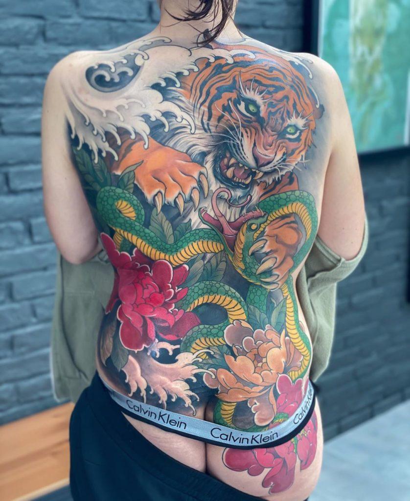 Tatuaż tygrys zwężem ikwiatami, falą wjapońskim stylu naplecach ipupie męski, kobiecy