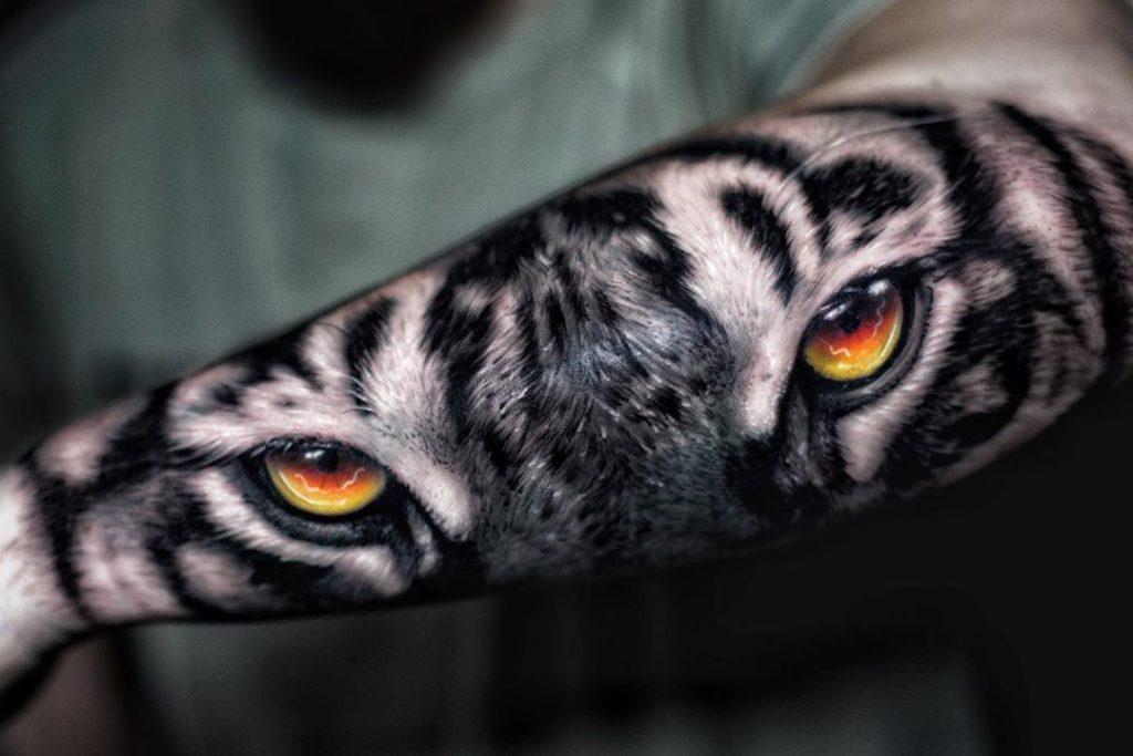 Tatuaż głowa oczy tygrysa zpomarańczowymi oczami naprzedramieniu dla mężczyzn ikobiet