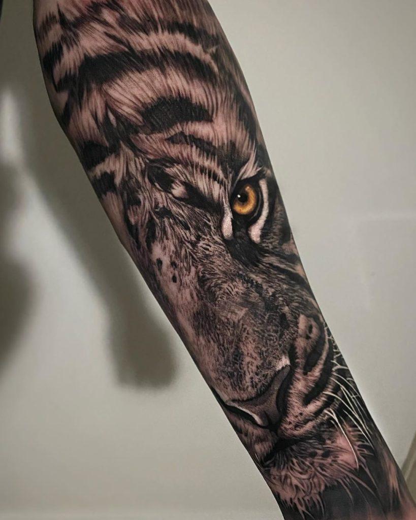 Tatuaż głowa tygrysa żółtym okiem naprzedramieniu dla mężczyzn ikobiet