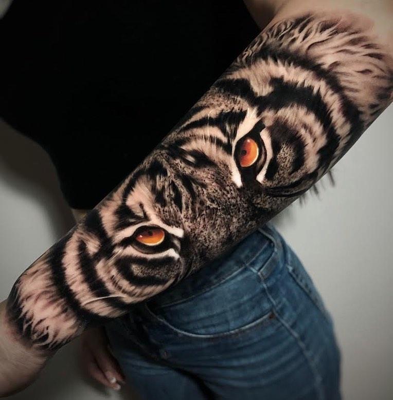 Tatuaż głowa tygrysa zpomarańczowymi oczami nazewnętrznej stronie przedramienia dla mężczyzn ikobiet