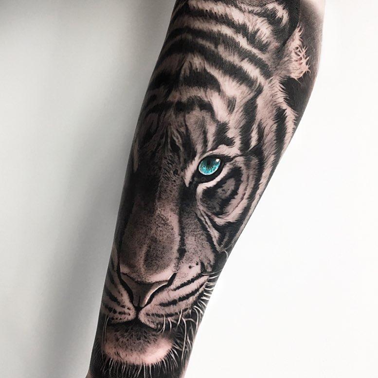 Tatuaż głowa tygrysa zniebieskimi oczami naprzedramieniu dla mężczyzn ikobiet